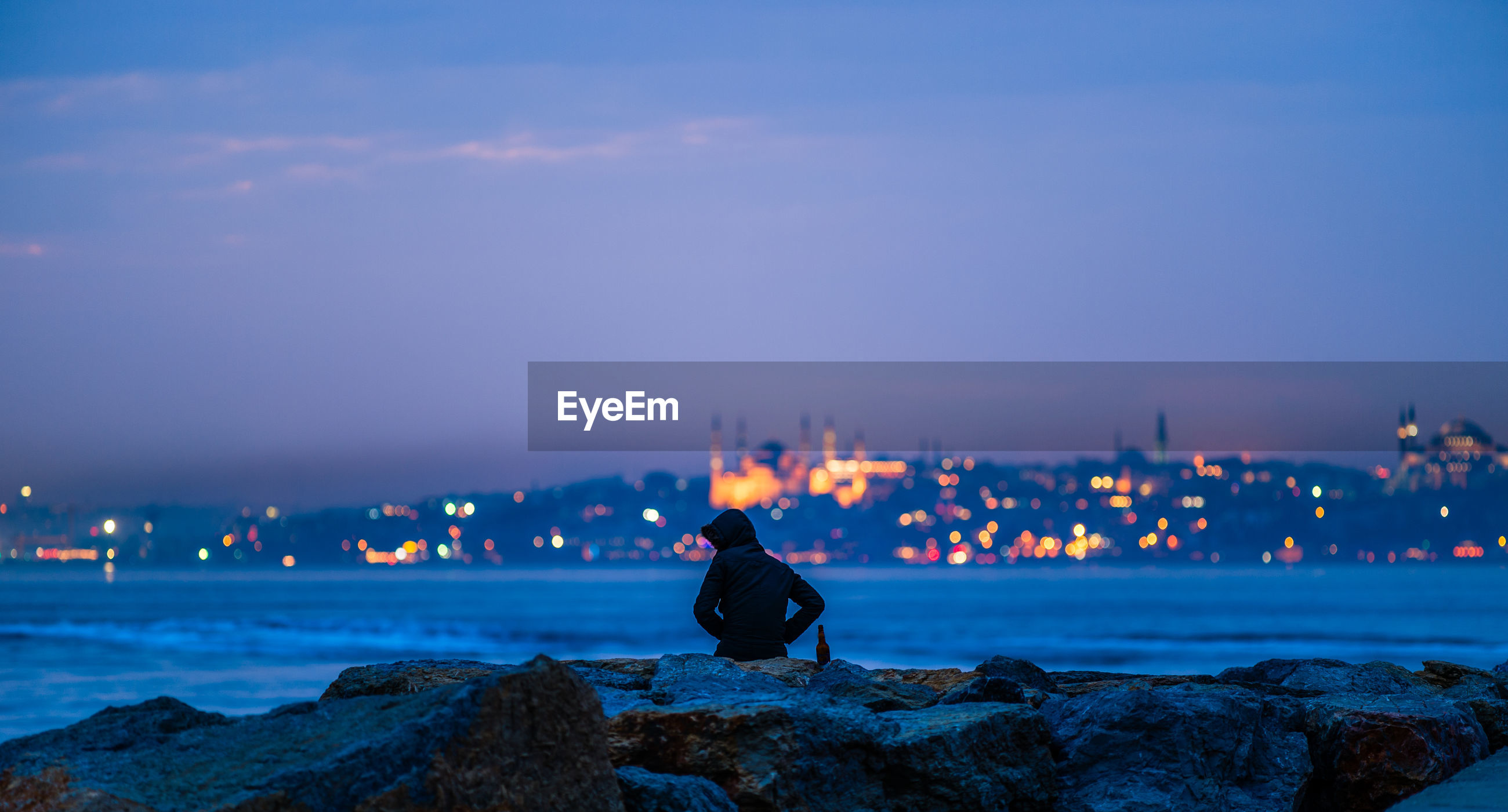 Hooded person sitting at rocky shore against sky at dusk