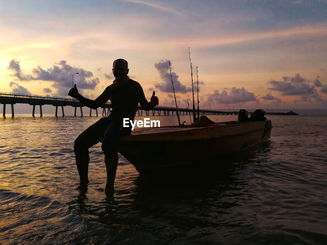 Silhouette man standing on boat in sea against sky during sunset