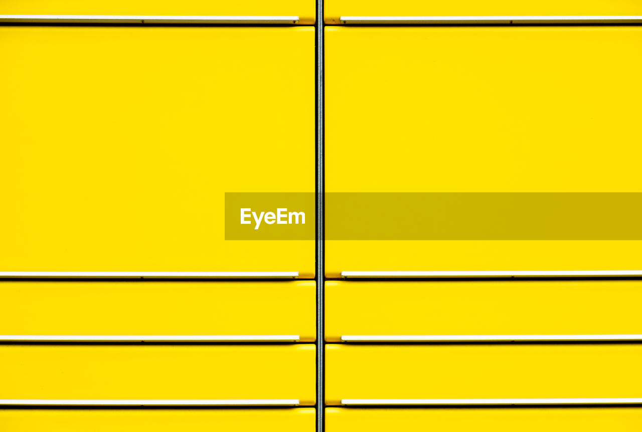 Full frame shot of yellow wall seen through metal grate