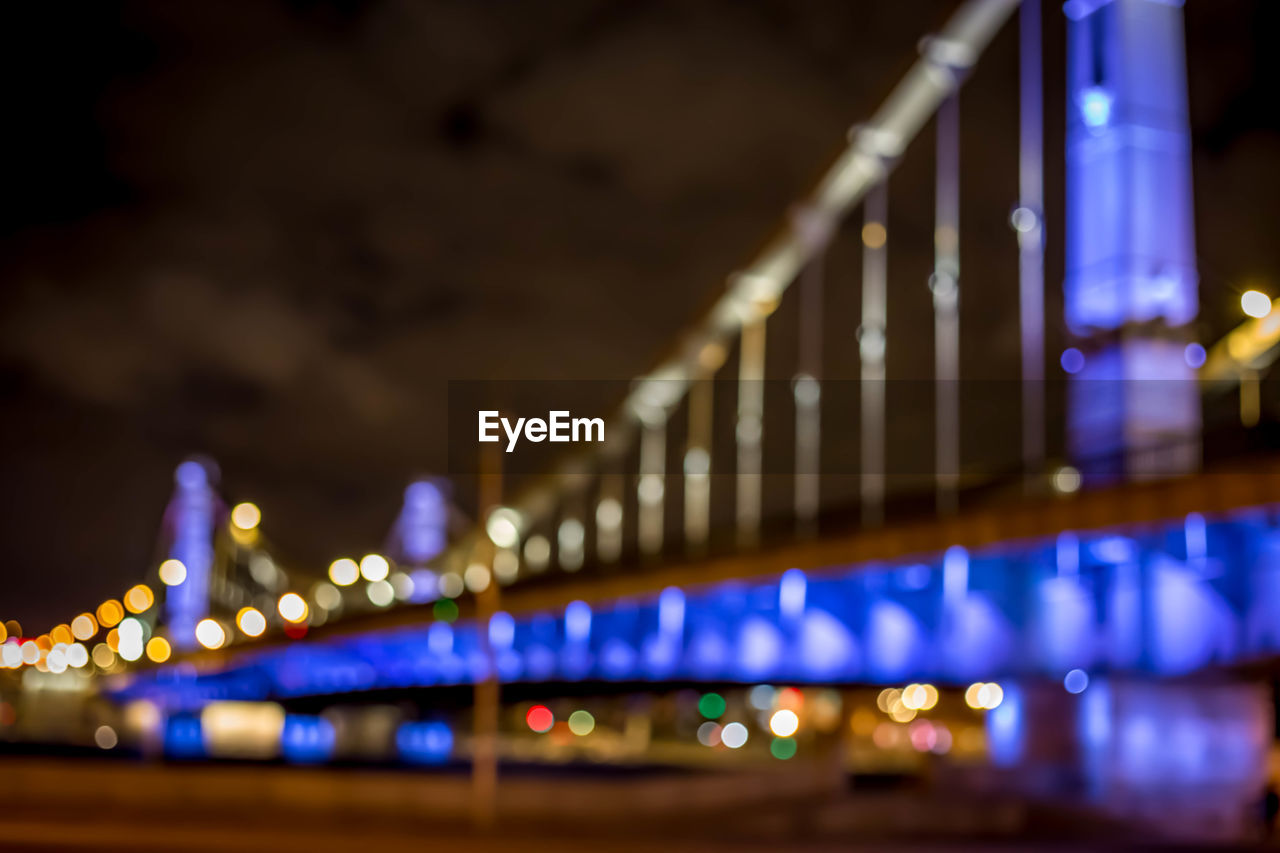 illuminated, built structure, connection, architecture, bridge, night, transportation, bridge - man made structure, city, glowing, engineering, focus on foreground, selective focus, travel destinations, lighting equipment, building exterior, outdoors, tourism, railing, light