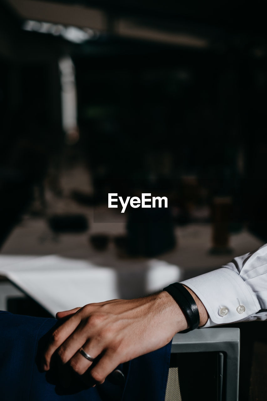 Cropped hand of businessman on desk in office