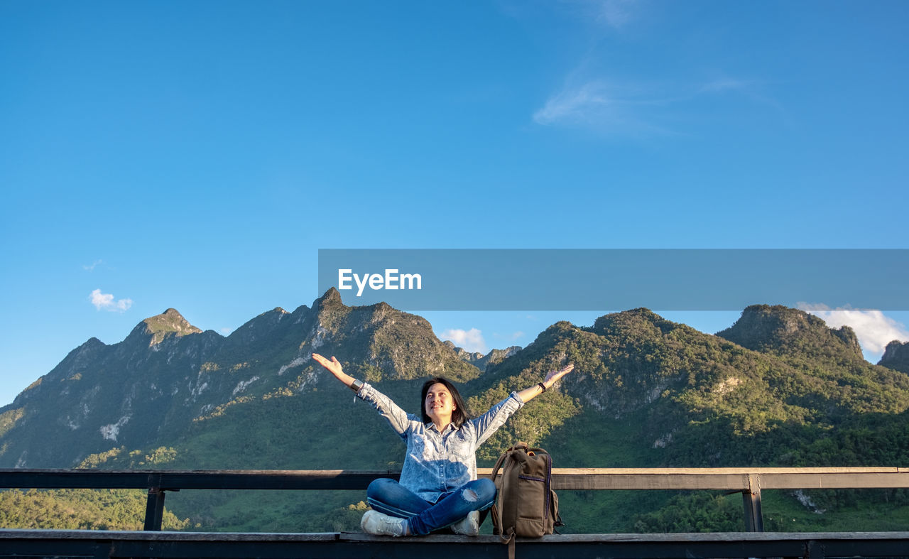 Woman with arms outstretched sitting by railing against blue sky