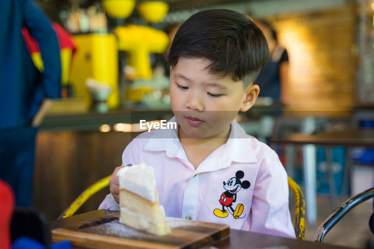 child, childhood, real people, men, boys, males, indoors, front view, holding, one person, lifestyles, table, focus on foreground, portrait, looking, headshot, casual clothing, cute, innocence