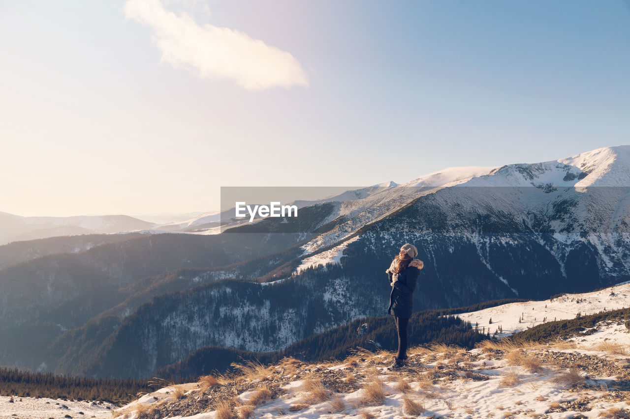 Side View Of Woman Standing Against Mountain And Sky During Winter