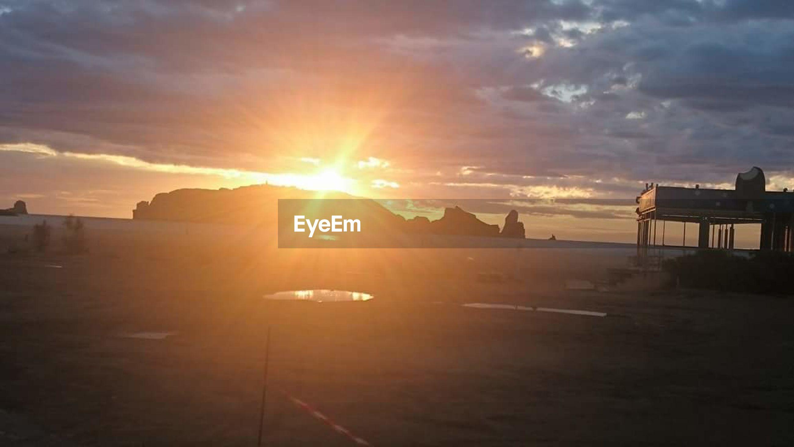 sunset, sky, cloud - sky, beauty in nature, sea, outdoors, nature, scenics, sunbeam, water, sun, no people, architecture, beach, day, passenger boarding bridge