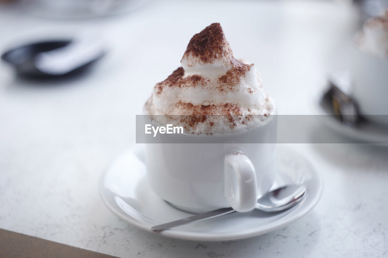 Close-Up Of Coffee With Froth In Cup On Table