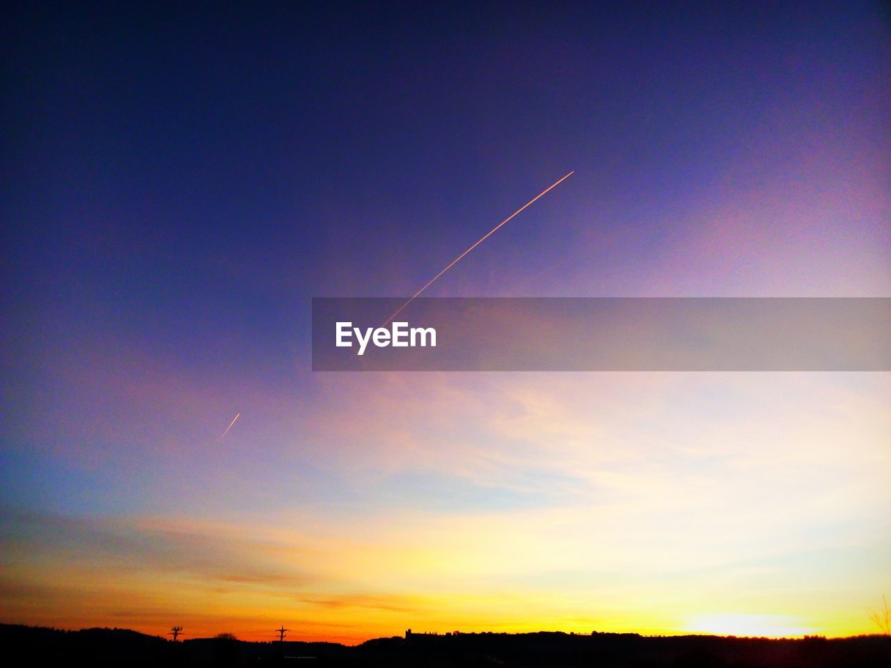 sky, cloud - sky, beauty in nature, sunset, vapor trail, scenics - nature, tranquility, tranquil scene, silhouette, nature, no people, orange color, idyllic, low angle view, landscape, environment, outdoors, blue, non-urban scene, dramatic sky