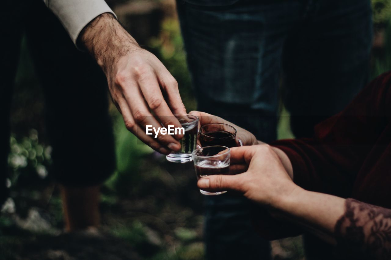 human hand, hand, holding, real people, midsection, human body part, men, focus on foreground, glass, people, drink, lifestyles, refreshment, leisure activity, food and drink, day, two people, alcohol, drinking glass