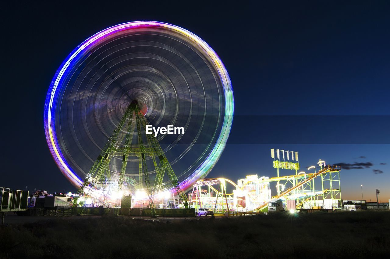 amusement park, arts culture and entertainment, amusement park ride, fairground ride, ferris wheel, fairground, night, illuminated, big wheel, clear sky, circle, ride, leisure activity, blue, motion, outdoors, low angle view, no people, fun, sky, multi colored, carousel, merry-go-round