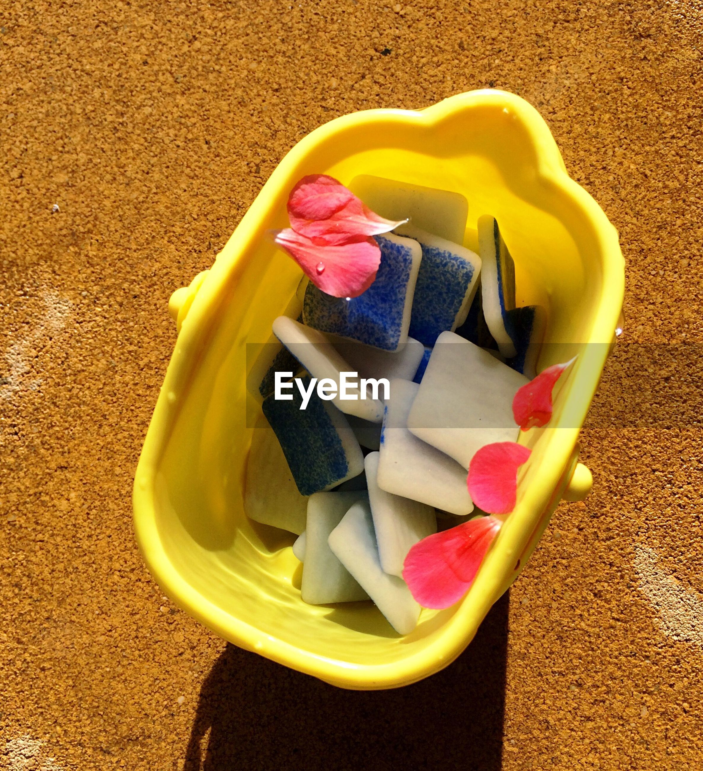 High angle view of toys in basket on beach during sunny day