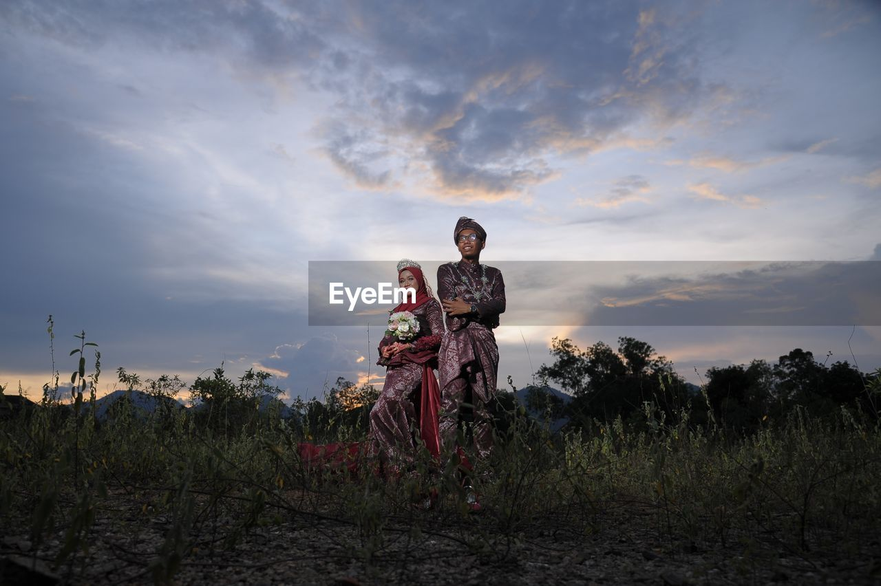 cloud - sky, sky, sunset, real people, land, standing, nature, field, men, males, people, child, togetherness, childhood, plant, leisure activity, family, lifestyles, two people, grass, outdoors