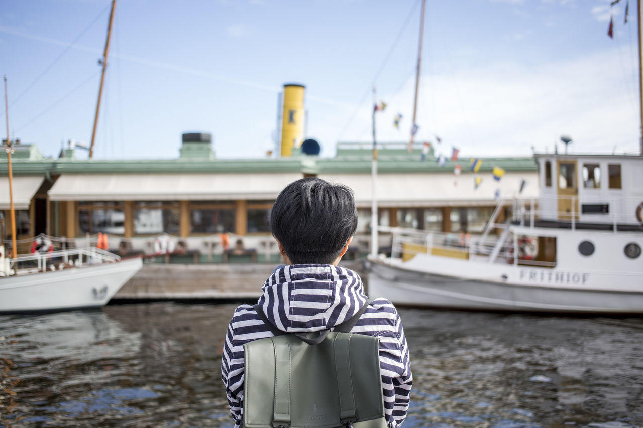 Rear View Of Man Standing Against Boats At Harbor In City