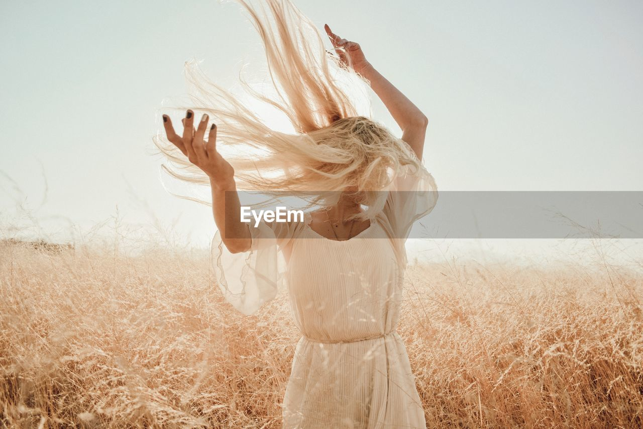 Woman Tossing Blond Hair While Standing On Grassy Field