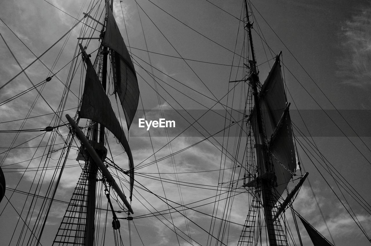 Low angle view of masts against sky