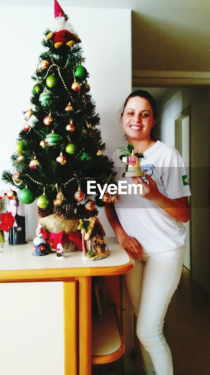 christmas, christmas tree, looking at camera, indoors, one person, smiling, celebration, tree, portrait, real people, young adult, christmas decoration, happiness, young women, home interior, full length, lifestyles, standing, cheerful, day, people