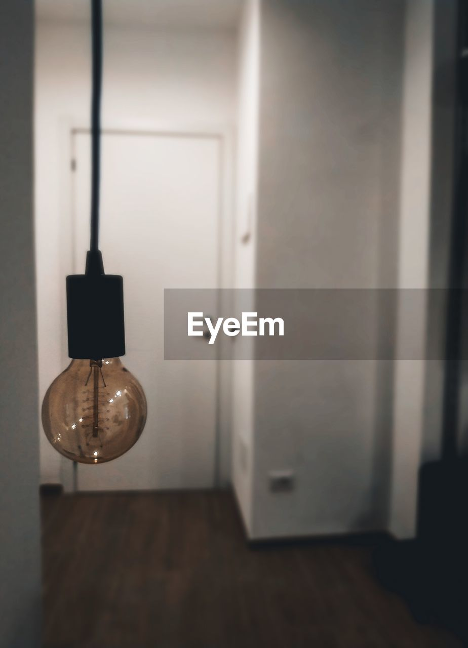 indoors, door, no people, entrance, wall - building feature, lighting equipment, hanging, focus on foreground, home interior, close-up, wood - material, illuminated, electricity, light, absence, flooring, open, light bulb, architecture, domestic room, electric lamp