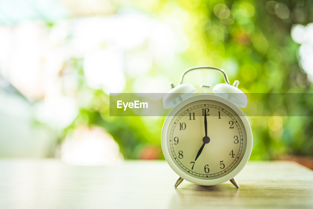 clock, time, alarm clock, focus on foreground, number, table, no people, close-up, clock face, day, still life, accuracy, instrument of time, shape, outdoors, single object, nature, deadline, minute hand