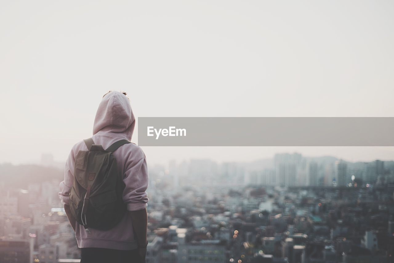Man Looking At Cityscape Against Sky