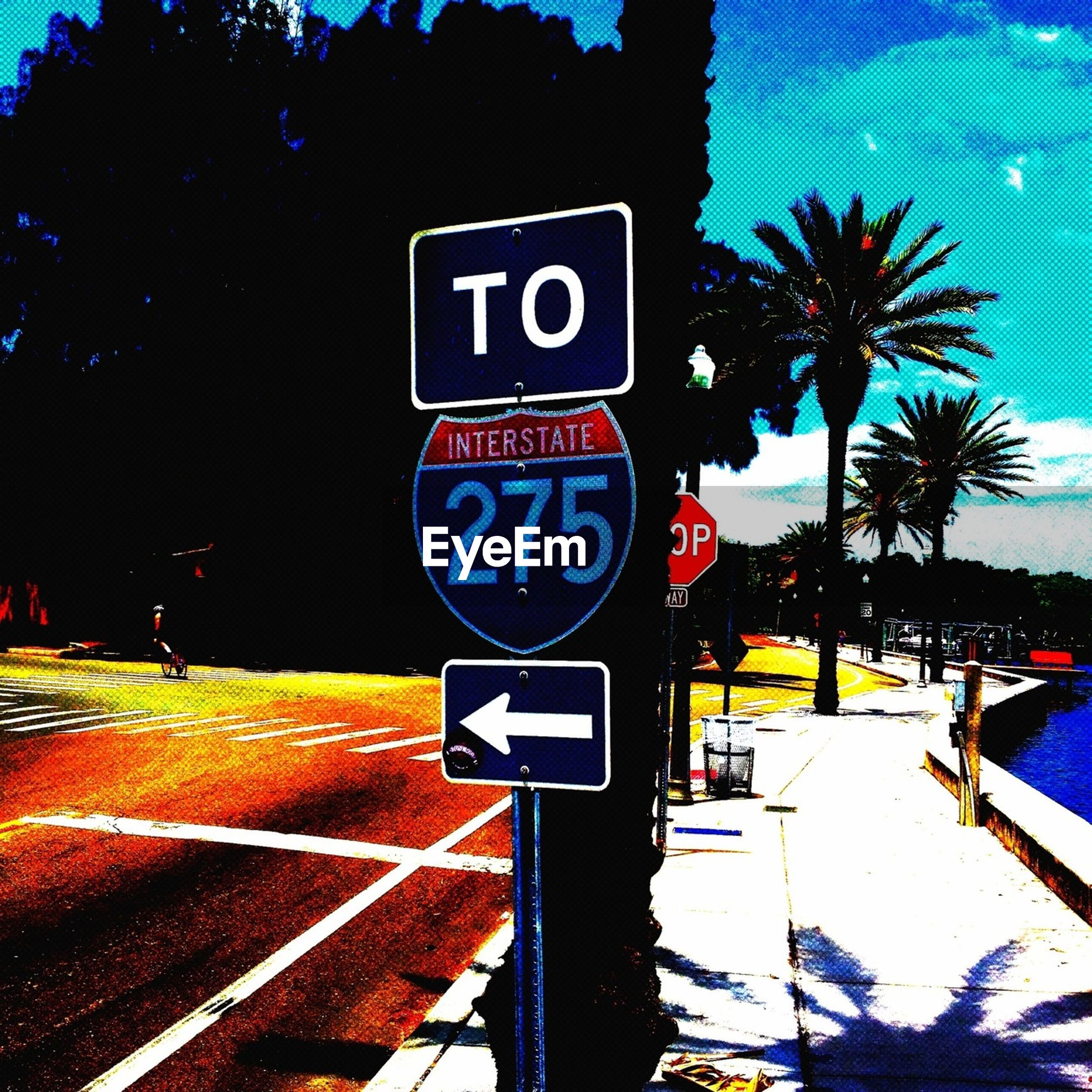 text, communication, western script, road sign, information sign, sign, capital letter, guidance, tree, transportation, illuminated, information, blue, street, warning sign, arrow symbol, directional sign, non-western script, road, incidental people