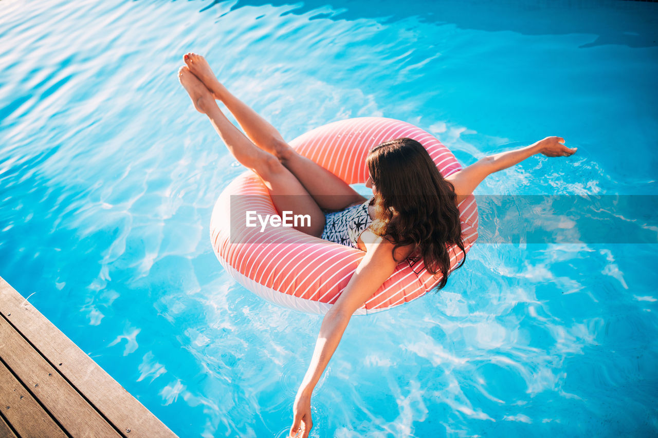 High Angle View Of Woman Sitting On Inflatable Ring Floating In Swimming Pool