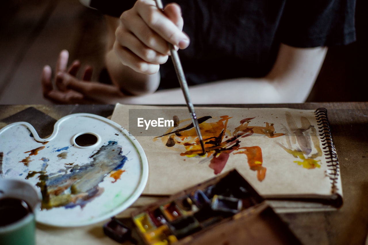 art and craft, creativity, brush, paintbrush, holding, human hand, occupation, selective focus, one person, indoors, real people, palette, paint, human body part, artist, hand, skill, table, craft, leisure activity, watercolor paints, art and craft equipment, finger