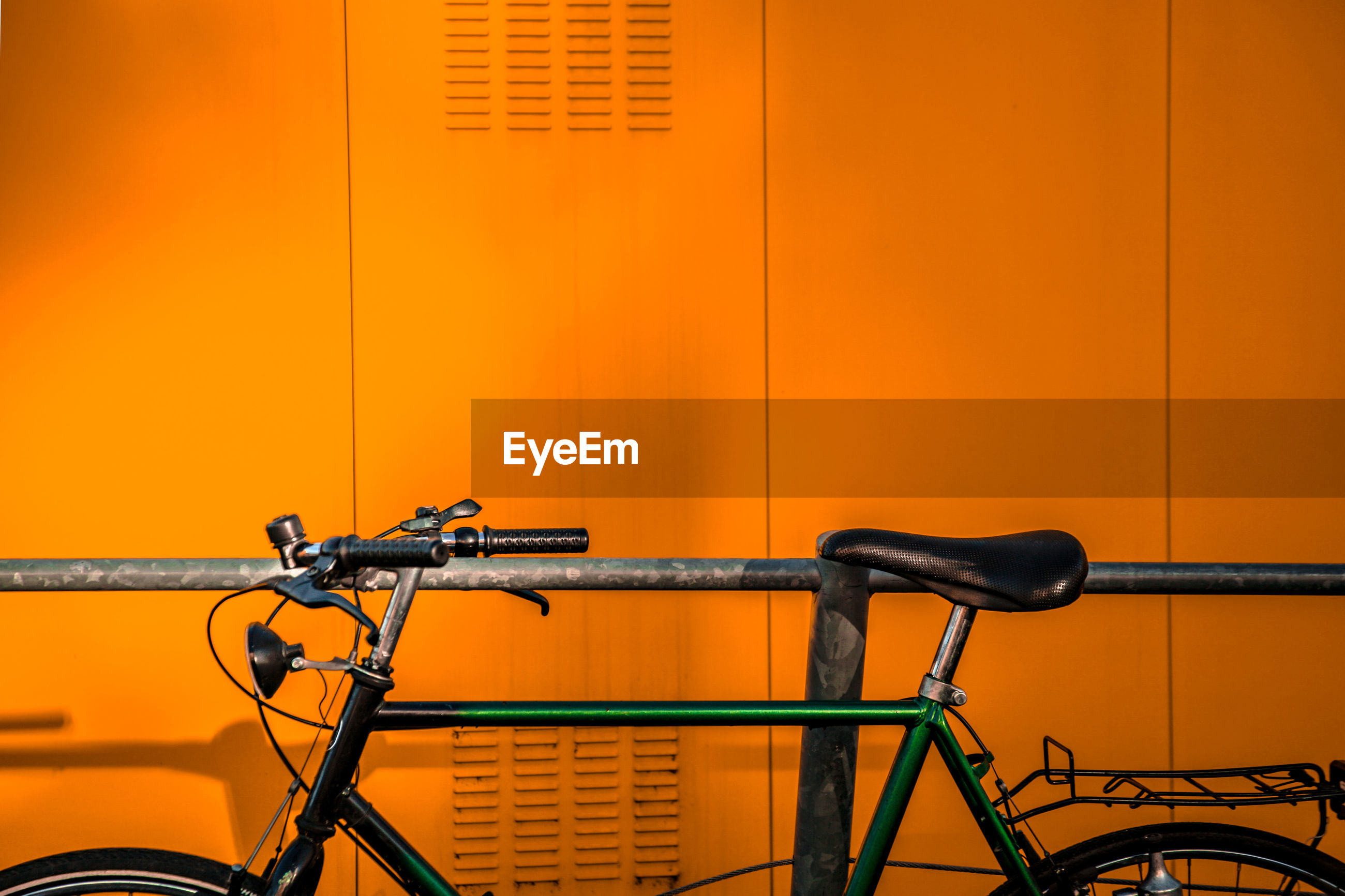 Close-up of bicycle against orange wall