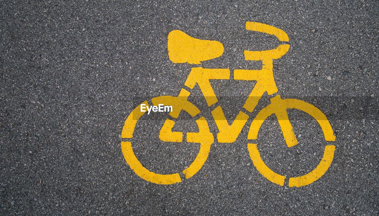 High angle view of yellow bicycle symbol on street