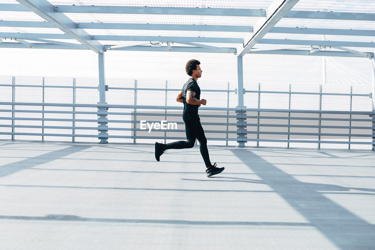 Side View Of Young Man Running On Footbridge