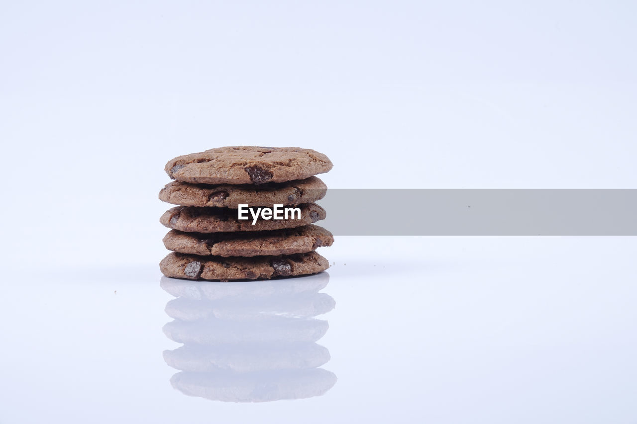 stack, food and drink, studio shot, white background, still life, sweet food, food, indoors, indulgence, freshness, baked, copy space, temptation, no people, cookie, ready-to-eat, unhealthy eating, close-up, sweet, dessert, snack, chocolate chip cookie