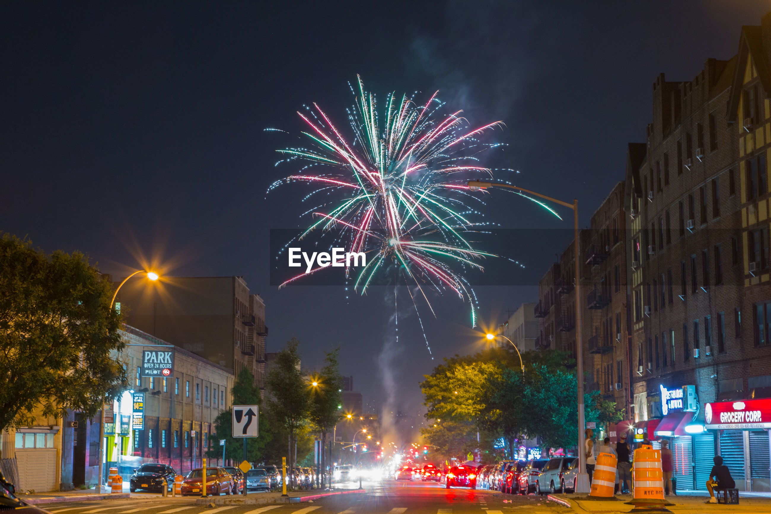 night, illuminated, firework display, celebration, blurred motion, motion, exploding, long exposure, firework - man made object, city, building exterior, architecture, arts culture and entertainment, street, outdoors, sky, city life, multi colored, low angle view, built structure, cityscape, firework, no people