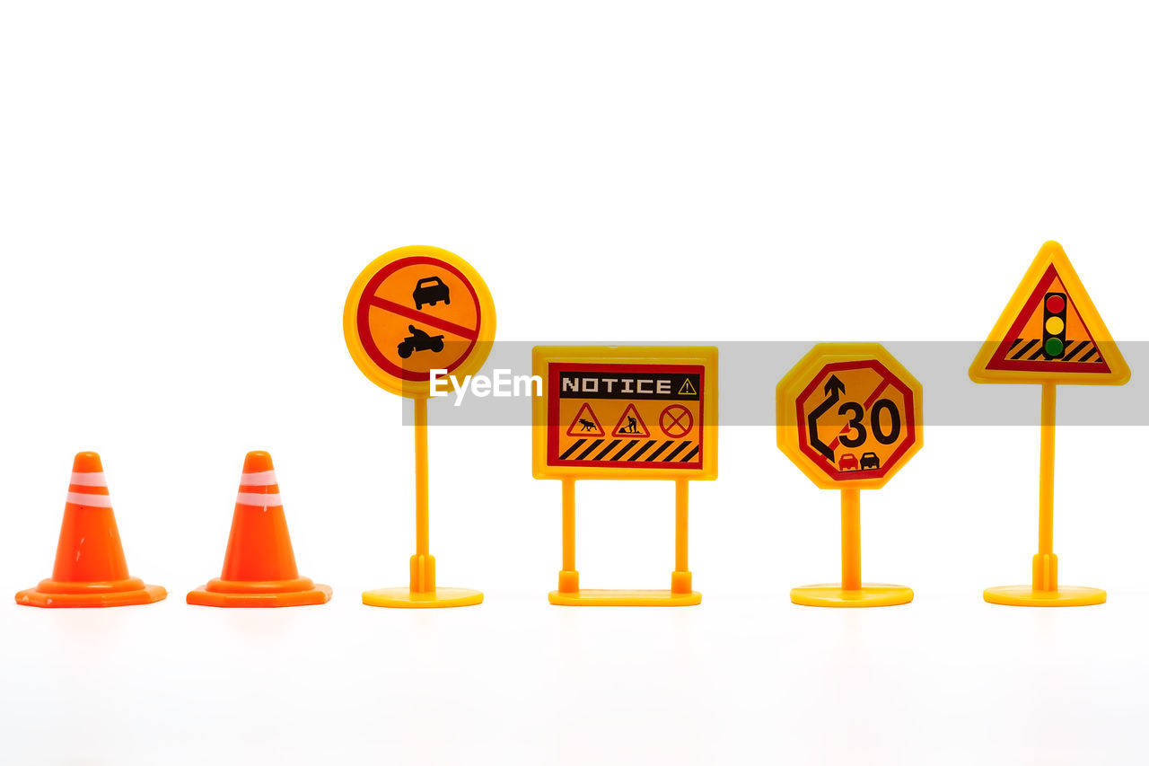 communication, text, sign, copy space, white background, western script, no people, studio shot, warning sign, indoors, still life, capital letter, orange color, yellow, guidance, road sign, cut out, information, side by side, traffic cone, rules, road warning sign