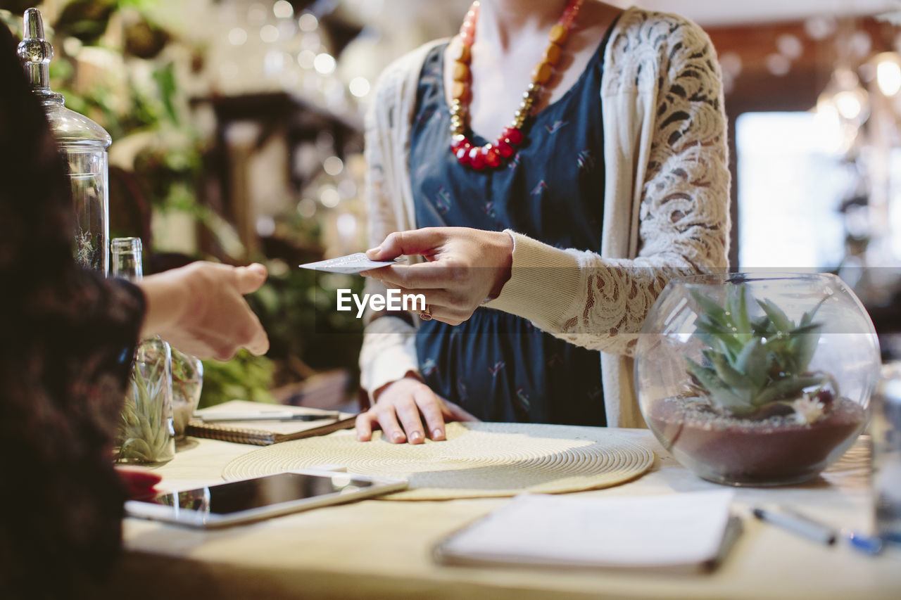 women, real people, midsection, adult, selective focus, occupation, business, indoors, food and drink, holding, table, two people, people, working, communication, standing, small business, pen, human hand