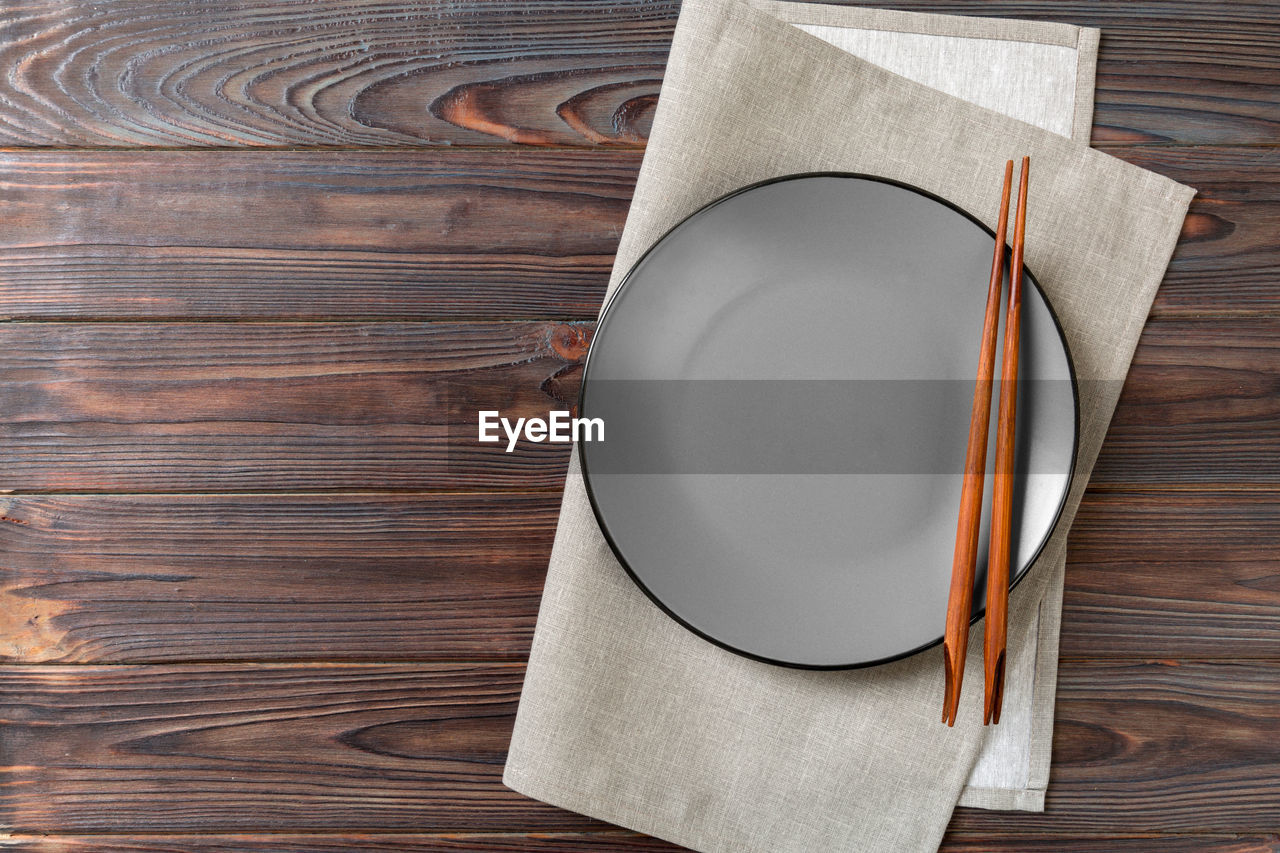 wood - material, table, directly above, still life, no people, high angle view, indoors, kitchen utensil, empty, napkin, close-up, brown, publication, pattern, book, household equipment, container, paper, food and drink, white color, blank, personal accessory, setting