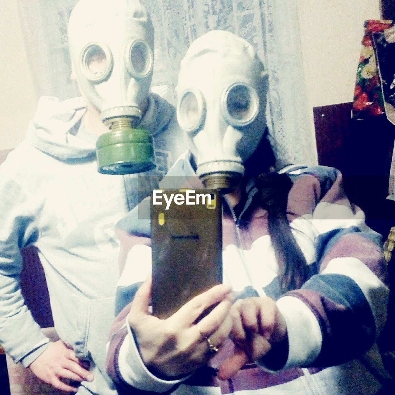 Friends wearing gas mask taking selfie at home