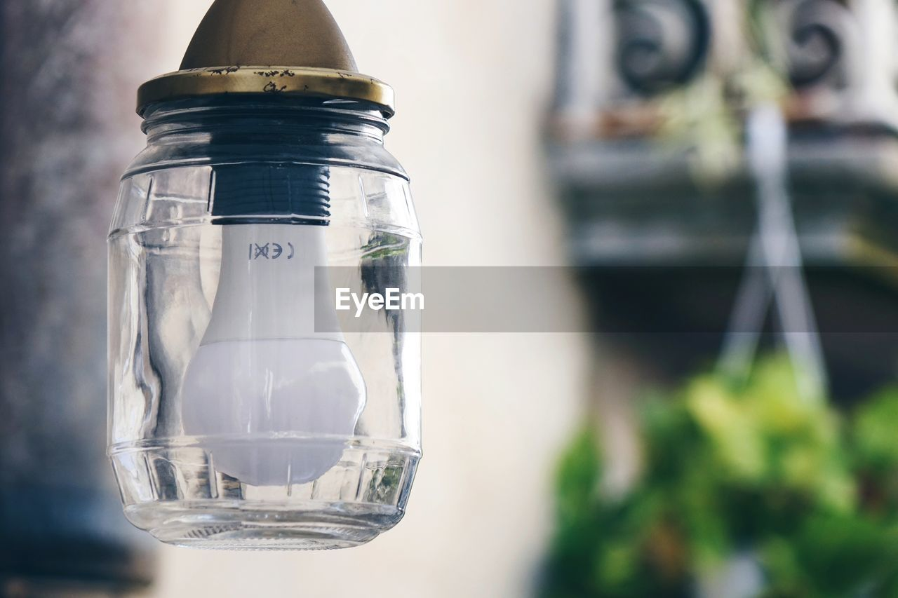 Close-up of light bulb hanging outdoors