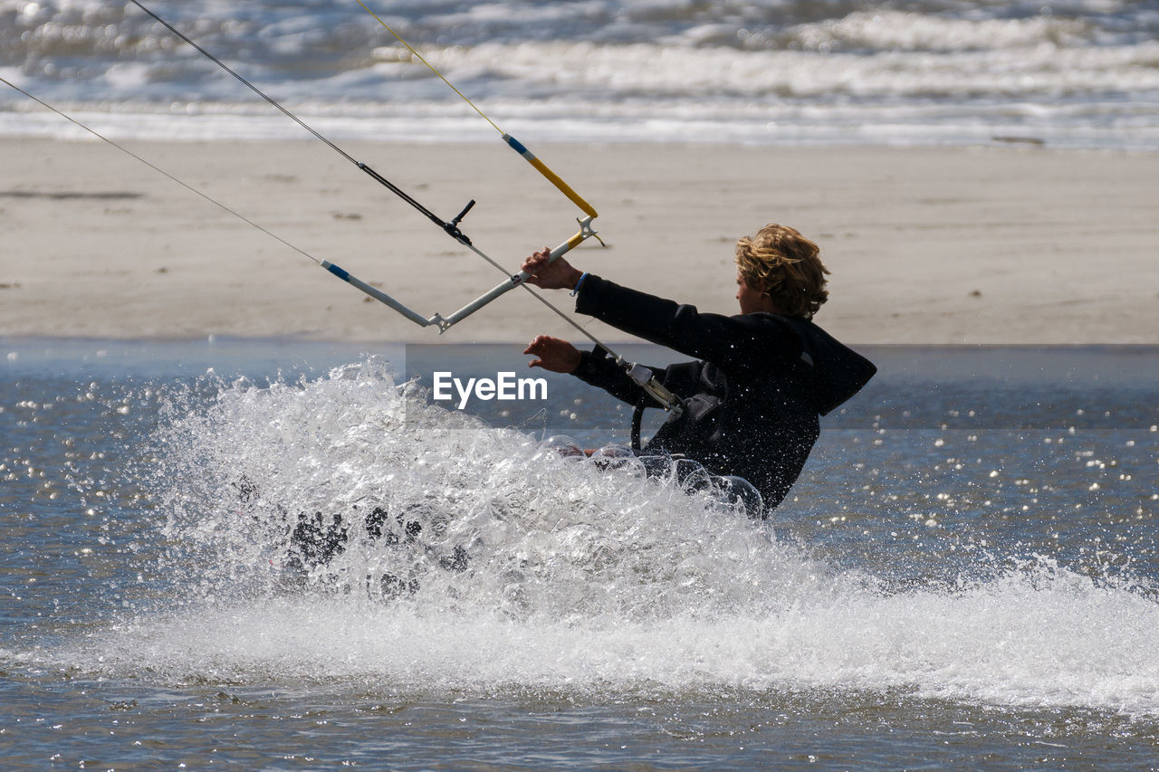 Side View Of Person Kiteboarding In Sea