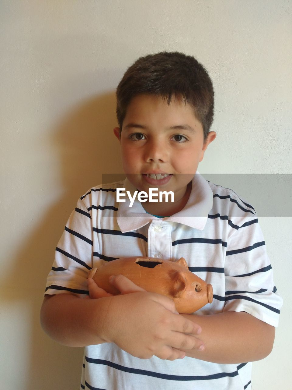 Portrait Of Boy Holding Piggy Bank Against White Wall