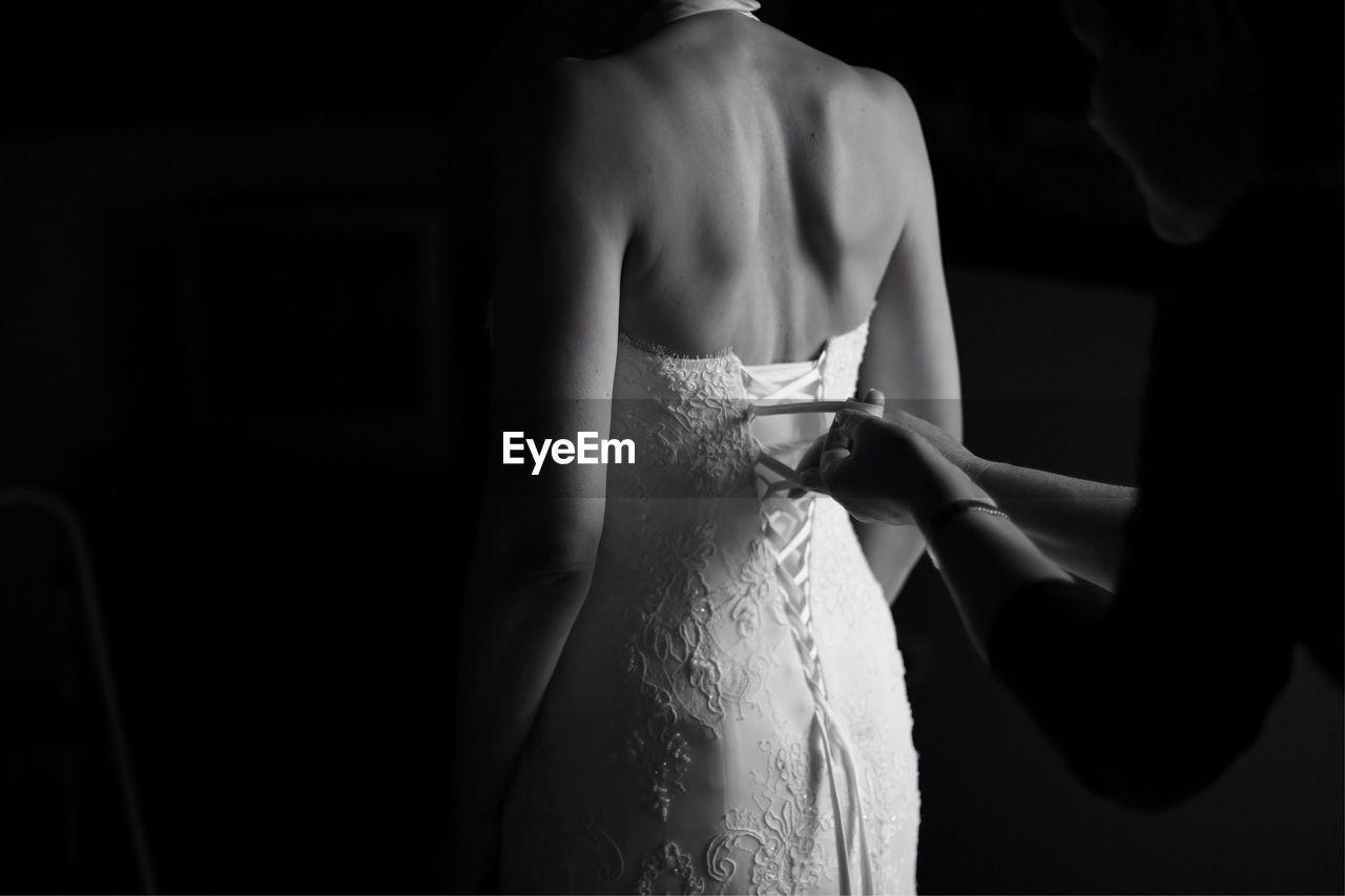 Woman helping bride in dressing