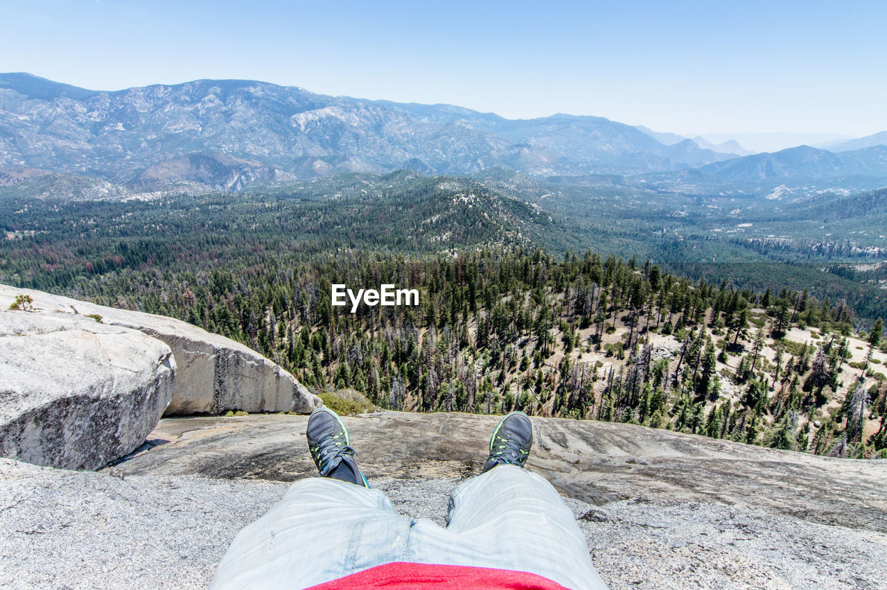 Low section of man lying on mountain against sky