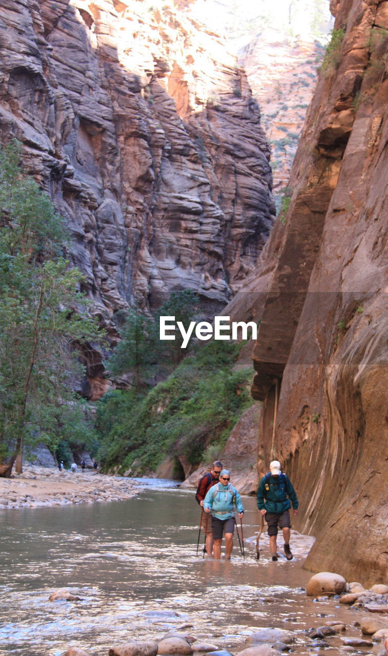 Hikers Walking By Rock Formation On River