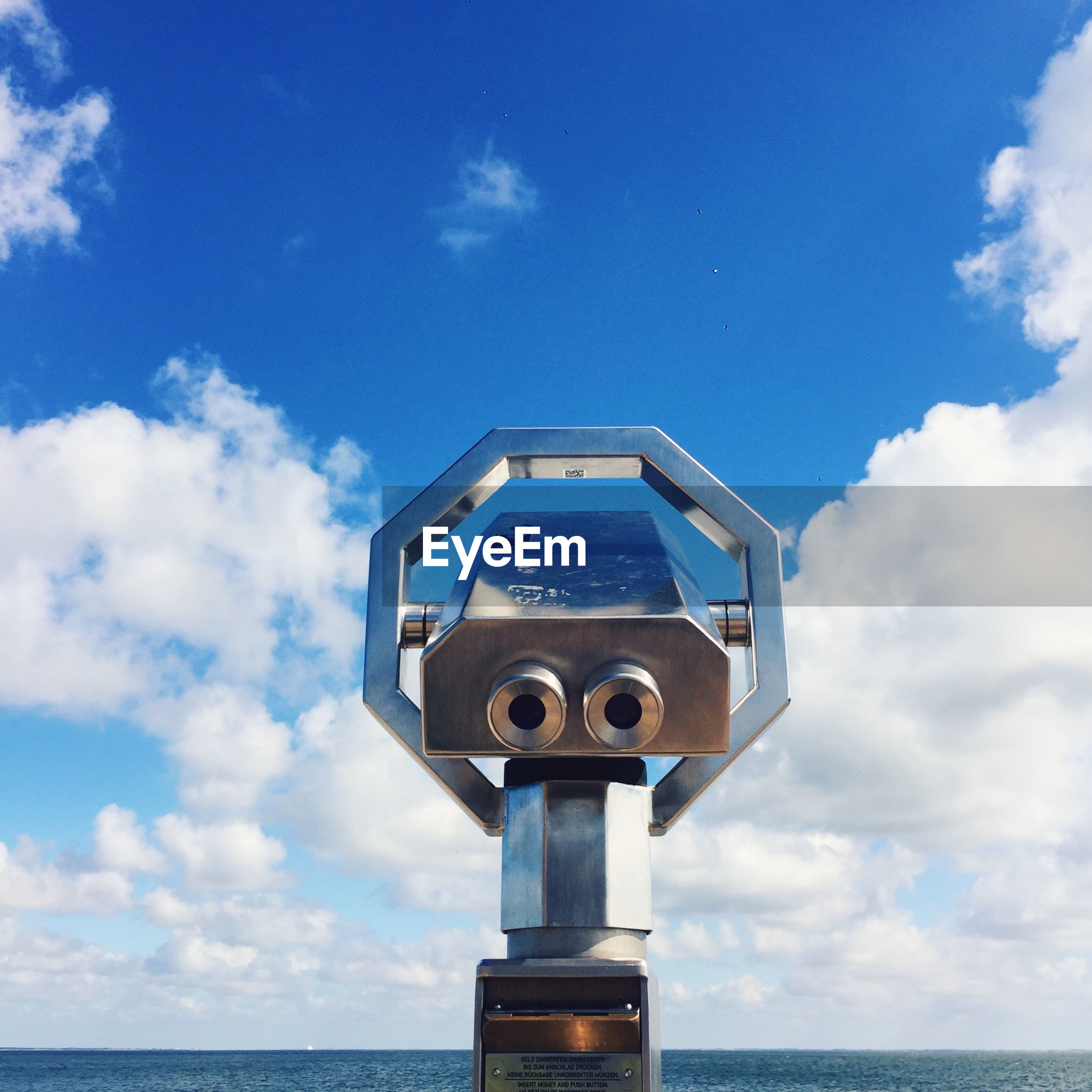 Coin-operated binoculars by sea against sky