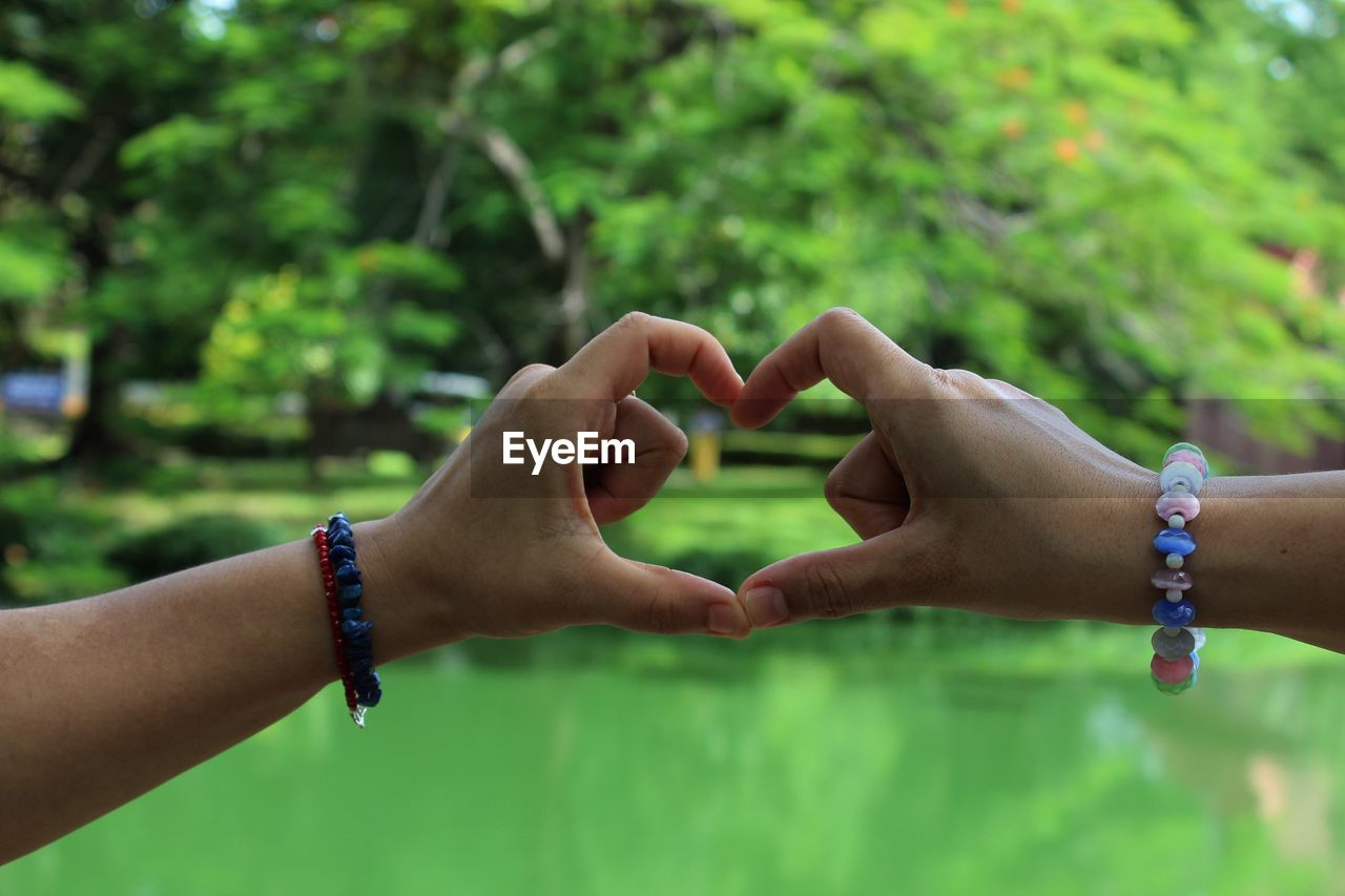 Cropped Image Of Hands Making Heart Shape At Park