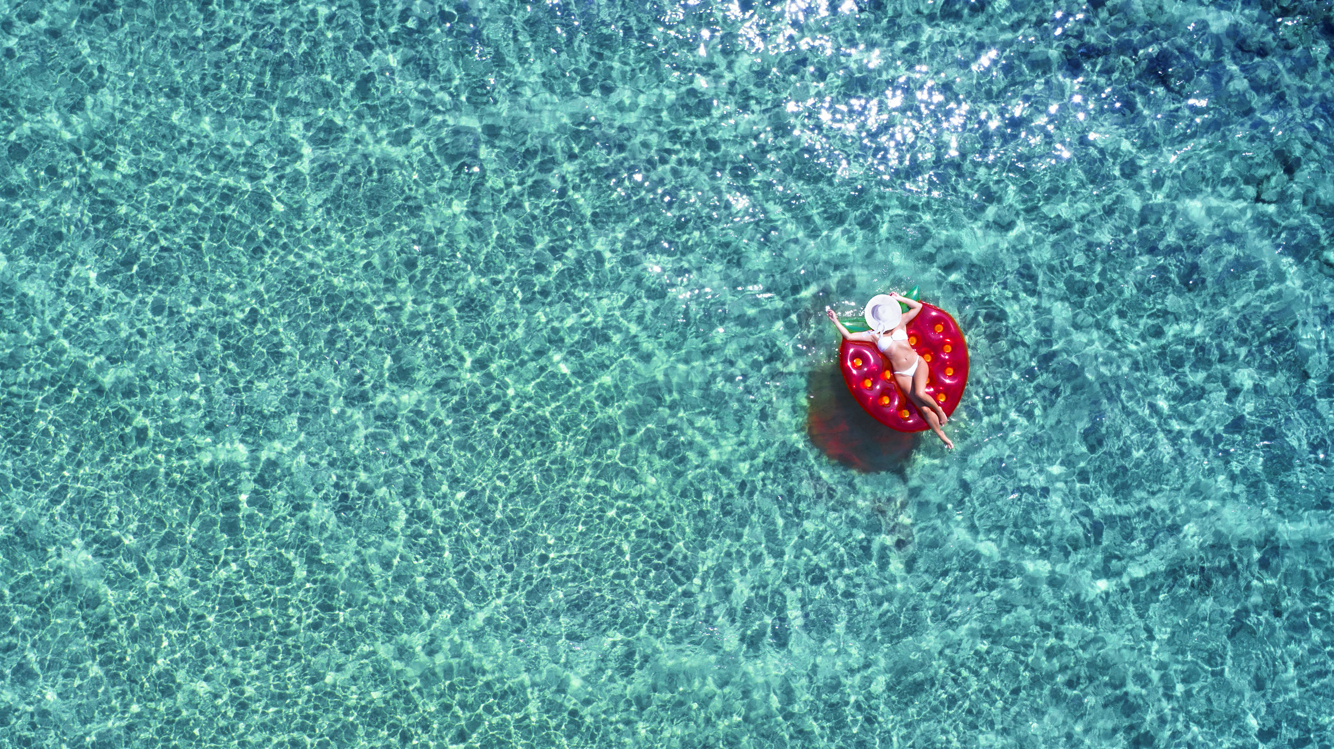High angle view of woman relaxing on pool raft over turquoise sea