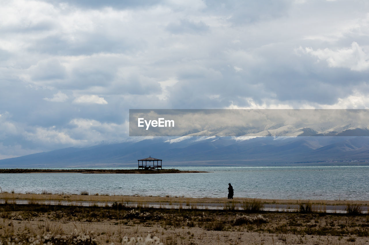cloud - sky, sky, water, sea, scenics - nature, beauty in nature, nature, tranquil scene, land, tranquility, day, one person, beach, real people, non-urban scene, men, outdoors, lifestyles