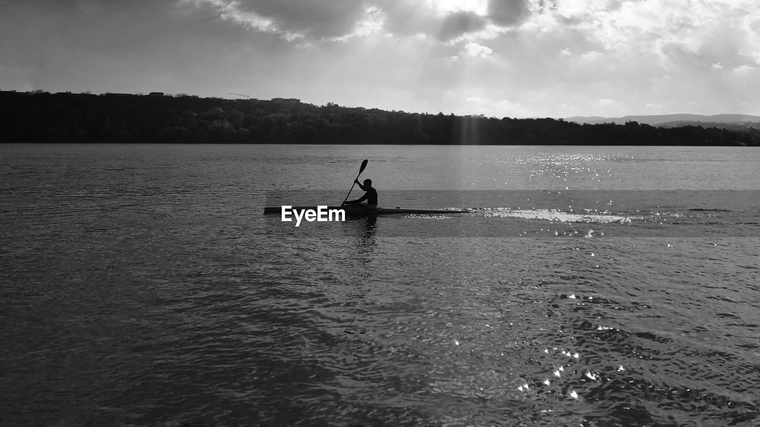 Silhouette man sculling in lake against sky