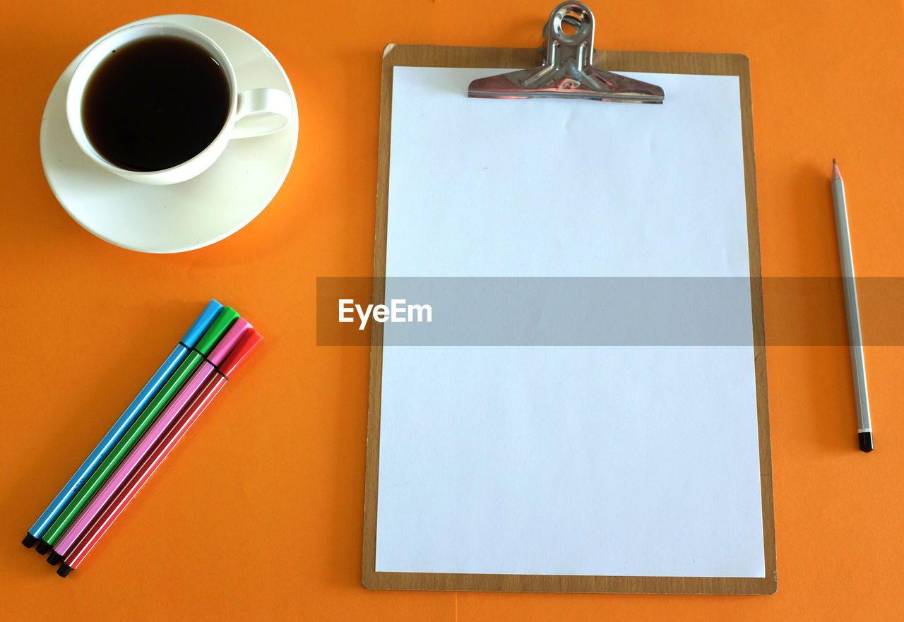 cup, table, coffee cup, coffee, mug, pen, indoors, coffee - drink, food and drink, drink, no people, still life, refreshment, high angle view, writing instrument, directly above, close-up, paper, pencil, book, blank