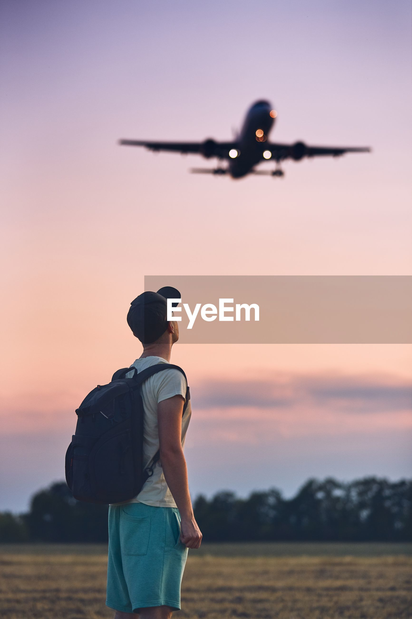 Side view of man with backpack looking at airplane against sky during sunset