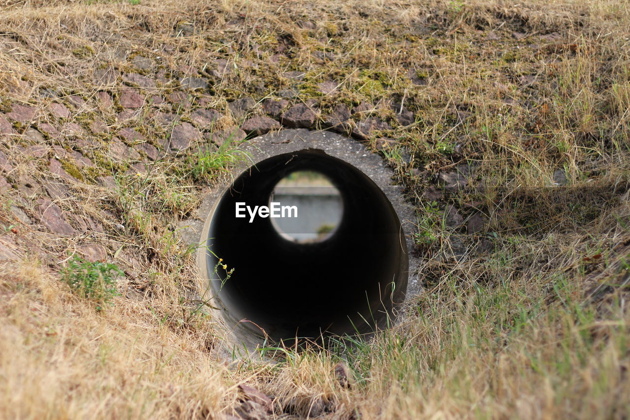 land, field, circle, grass, day, geometric shape, hole, plant, no people, nature, pipe - tube, shape, outdoors, selective focus, environment, old, dirt, pipe, abandoned, wheel