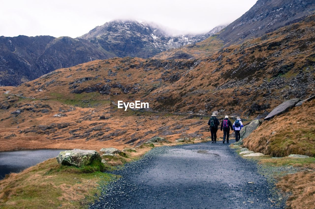 Rear View Of People Hiking Through Mountains Of Snowdonia, Wales