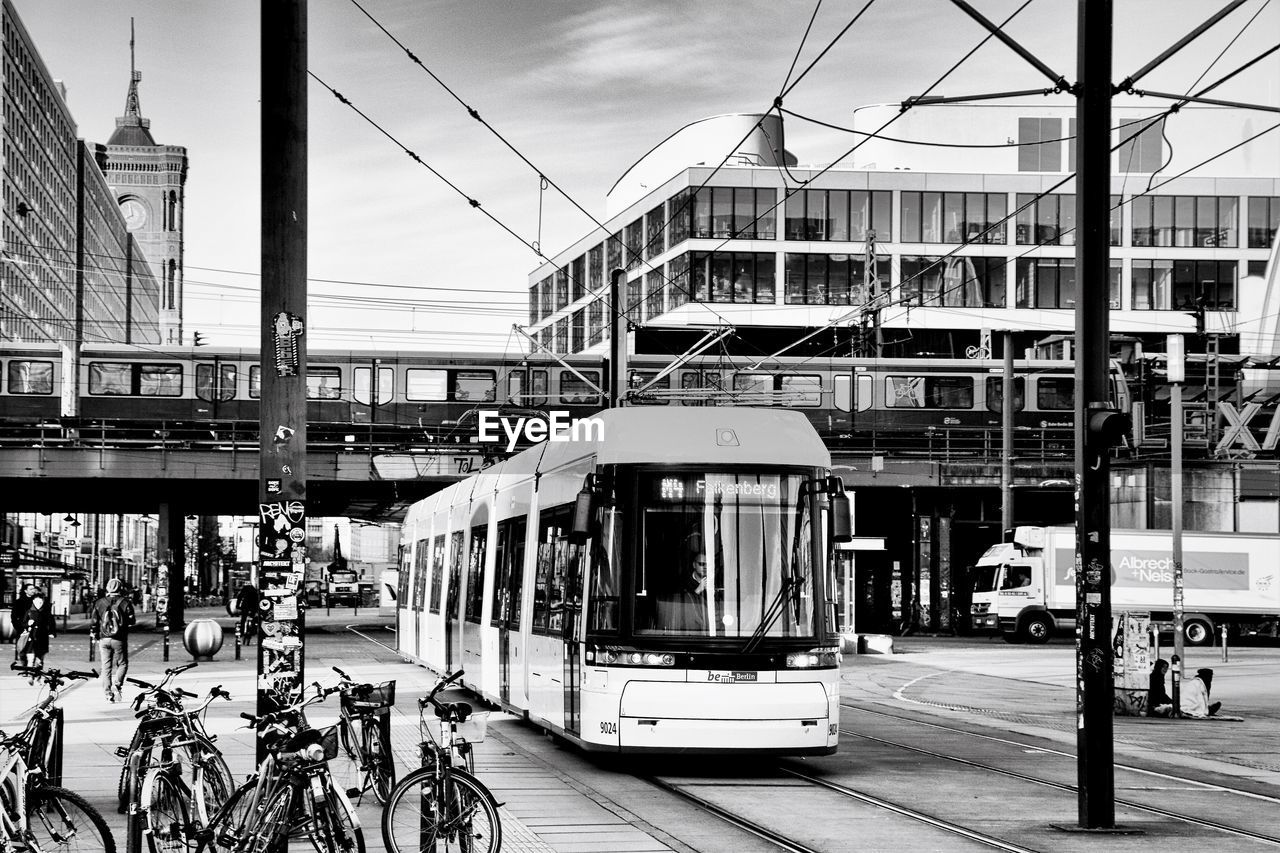 transportation, mode of transport, architecture, built structure, land vehicle, building exterior, day, public transportation, sky, bicycle, city, cable, outdoors, real people, road